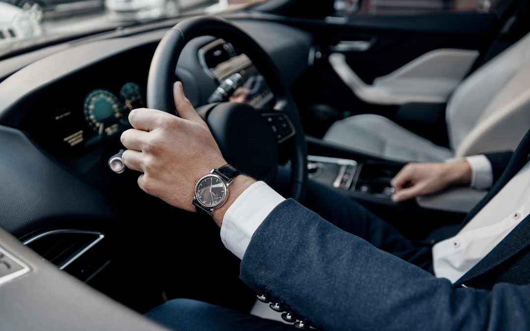 Great car. Close up top view of young man in formalwear keeping hand on the steering wheel while driving a luxury car